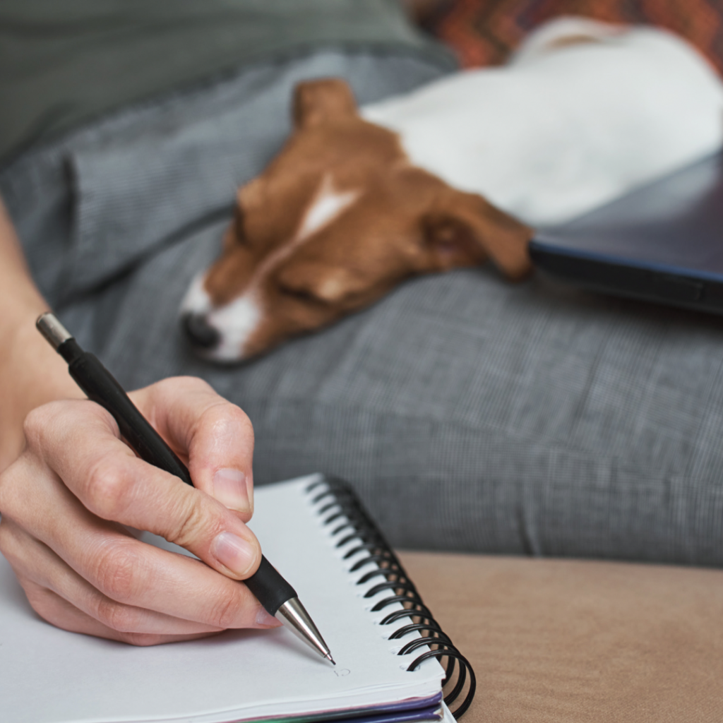 person writing and their dog on their lap