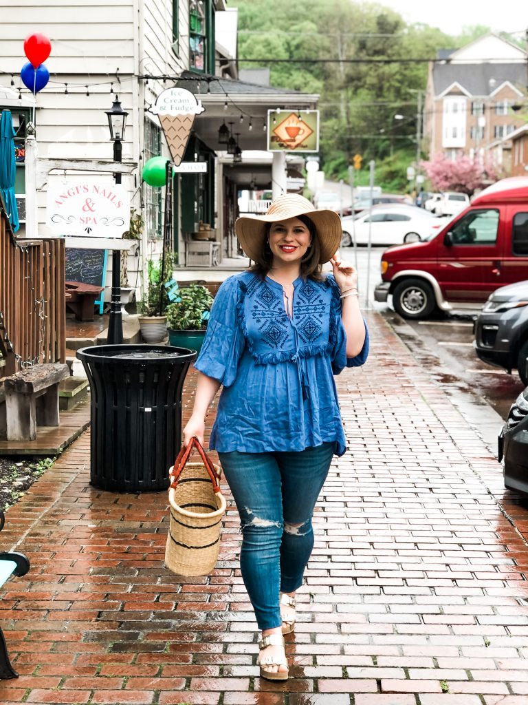 woman walking on the streets wearing a hat, blue top, and jeans